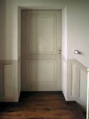 tipologia di porta più semplice, decorazione armonizzata con la finta boiserie in evidenza sul muro